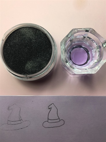 I used the same outline/sandwich bag technique with my 3-D witch hat. I had a very particular way I wanted the hat to look, so the hint mentioned in Step 5 would not work here unless I was able to find an exact image of the hat on Google. **HELPFUL HINT: Place a small piece of tape on the back of the outline before you place the paper in the sandwich bag. This will prevent the paper from sliding around underneath while you are sculpting. Once I finished sculpting my 3-D elements, I blinged them out with Swarovski Crystals.