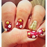 Red Nails With Goldfinger And Flowers