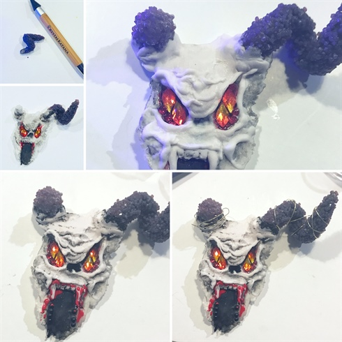 Ive used the end of my 3d brush to create texture when the acrylic is 50/50 dry. For the horns I've painted them in black gel and attached the purple crystal pixie with matte top coat. Horns are attached with clear acrylic, and I build up with white around the base. Ive used a mix of the crystals for his eyes, used black to shade areas. And added some black balls and red gel paint for detailing. Ive used fine picture hanging wire for around the horns.