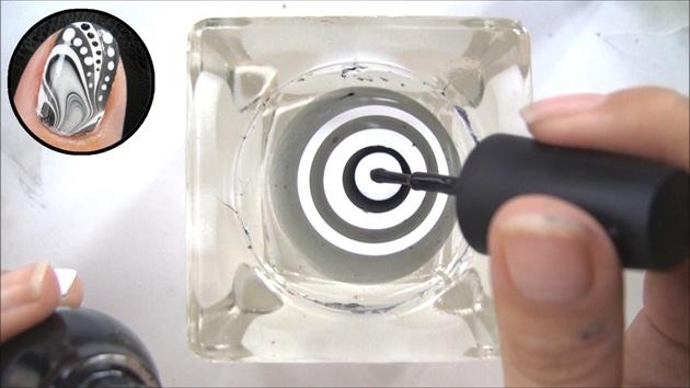drip black and white polish into room temperature water