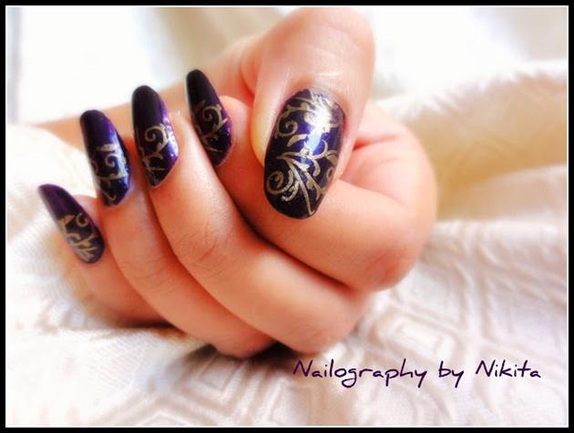 Stamped golden design on purple nails