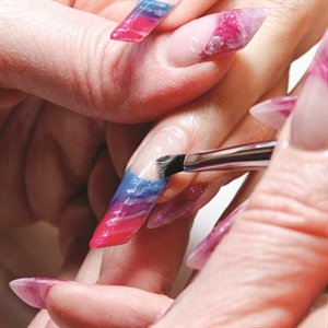 Pick up a small amount of Guilty Pleasure Gel Polish on one side of the brush and lightly drag the tip of  the brush, at an angle, through the pink, purple, and blue, cleaning off the brush and picking up more Guilty Pleasure between each color. Use a Light Elegance Smile Line brush to swipe a nice, crisp smile line. Flash cure each nail for 15 seconds. When all five are complete, cure for two minutes.