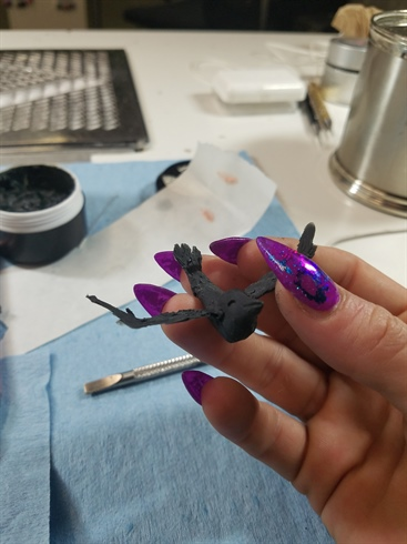 Using Gelish Polygel and Wildflowers Lace Paste, I sculpted a 3-D crow. I wore gloves to keep the mixture from sticking to my hands, and molded it like clay, curing it in my LED lamp for 120 seconds. For the eyes I used SS16 scarlet Swarovski crystals. Black details were added to the crystals.