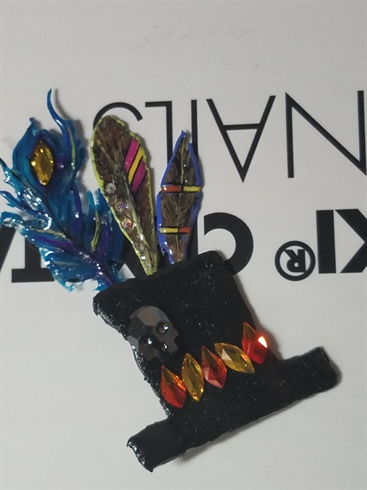 Feathers attached to hat with acrylic. Swarovski crystals attached to hat and feathers using En Vogue resin. Crystals used: sunflower, fire opal, crystal AB, hematite skull.
